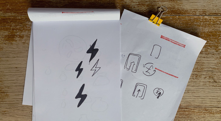 A sketchpad with some electric bolt icons doodled in pen