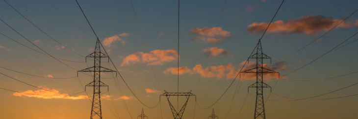 A picture of electricity poles at sunset