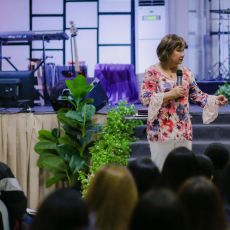 Cristina Sosso speaking on an elevated platform in front of the crowd at Christ Fellowship Church International (CCFI) in General Santos City.