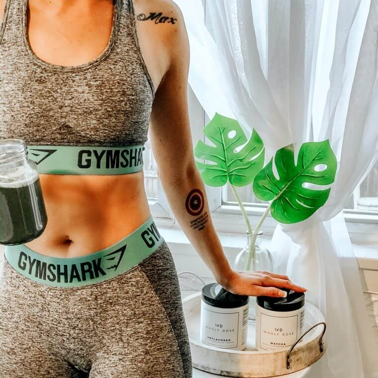 Woman in athletic wear posing next to two jars of Wholy Dose