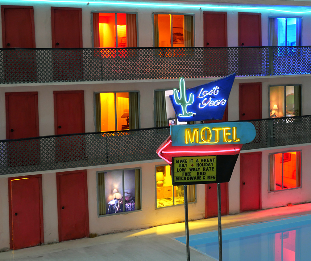 <em>Lost Year Motel</em>, 2020. Wood, plaster, paint, metal, lights, fabric, lcd screens, media players, electroluminescent wire, water, speakers, transformer. 24 x 50 x 24 in.
