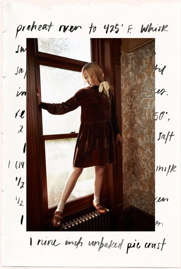 model in windowsill wearing brown velvet dress.