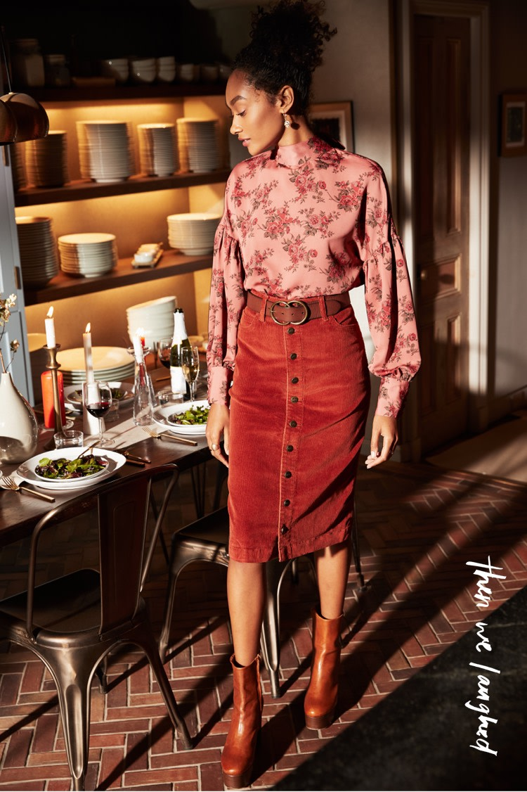 Pair a patterned blouse with a midi corduroy skirt and ankle booties.