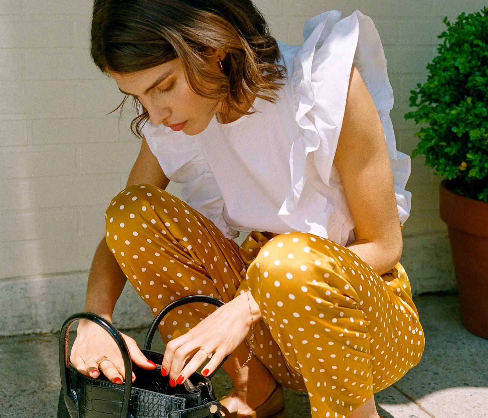 A white ruffled blouse and yellow polka dot trousers, taking you from work to cocktails.