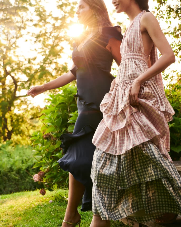 Two models walking through a garden wearing gowns.