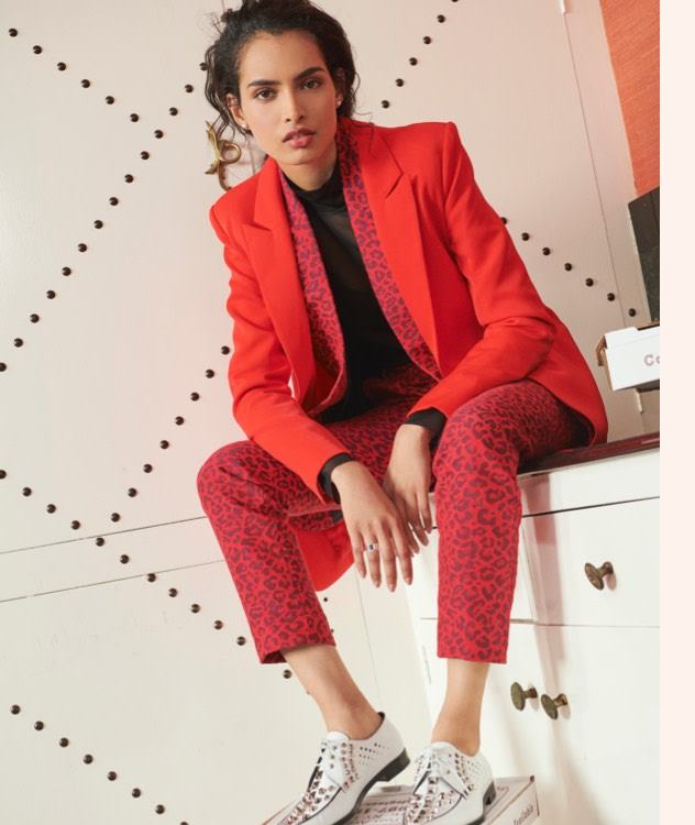 Layer red blazers with animal print slacks for a bold look.
