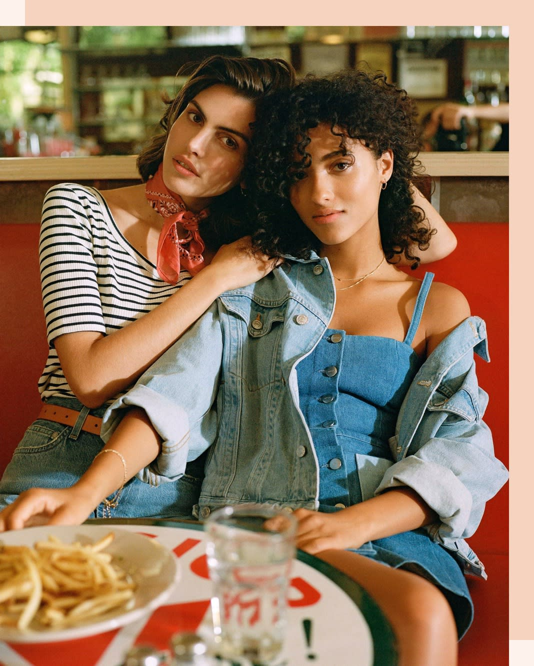 Two friends wearing denim, having dinner. Layer a denim jacket over a denim mini dress!