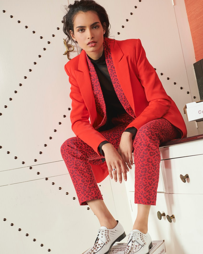 Layering red blazers with animal print pants.
