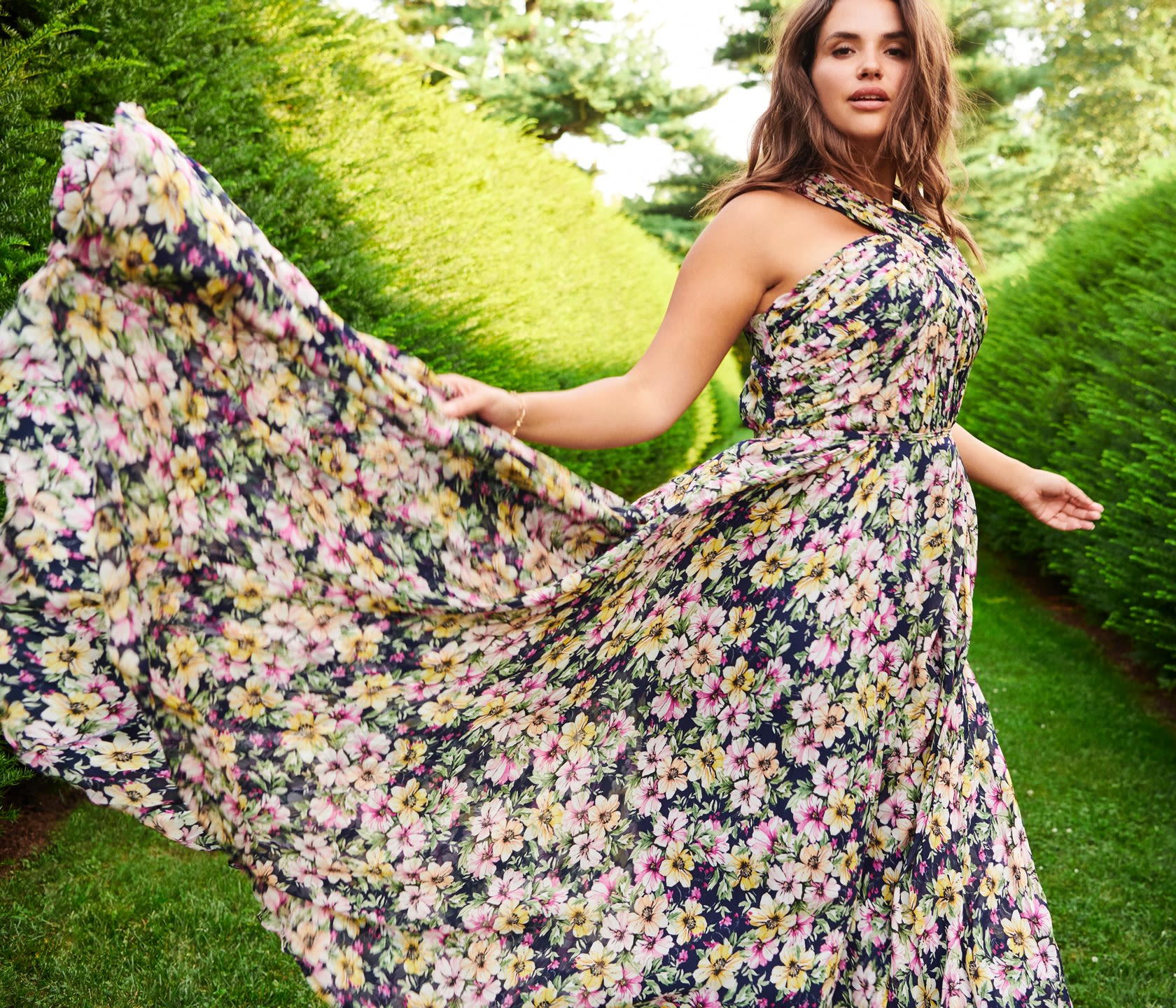 Model with a floral, colorful, and windswept dress walking through a graden.