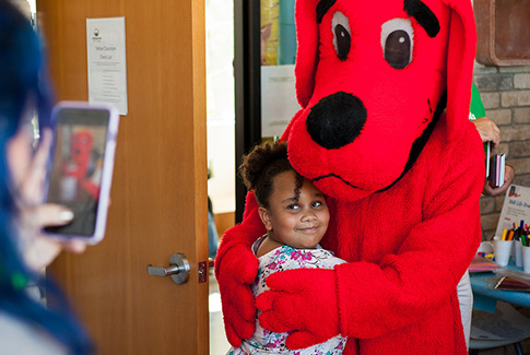 A child hugging Clifford the Big Red Dog while an adult, in the foreground, takes a picture on a smart phone.