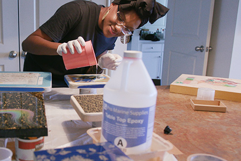 A woman, wearing gloves, pouring liquid from a cup as part of an at-home craft project. There is a bottle labeled Table Top Epoxy in the foreground.