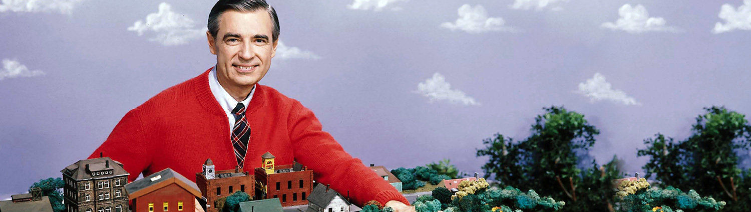 Fred Rogers wearing a red carding, smiling, with his miniature neighborhood..