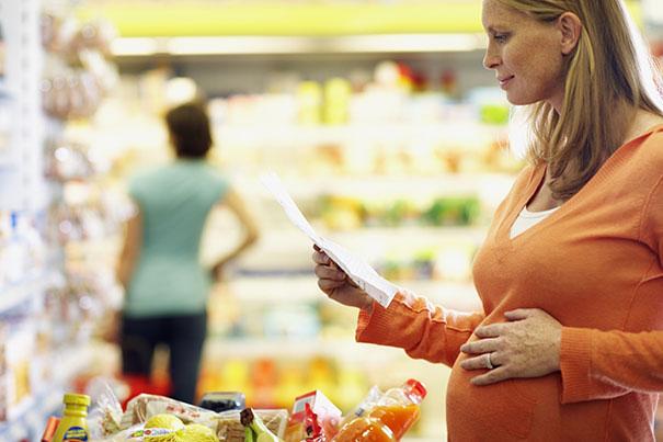 Schwangere Frau mit Einkaufsliste für eine gesunde Ernährung in der Schwangerschaft
