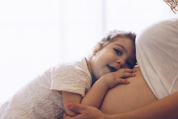 Kleinkind horcht am Bauch der schwangeren Mutter