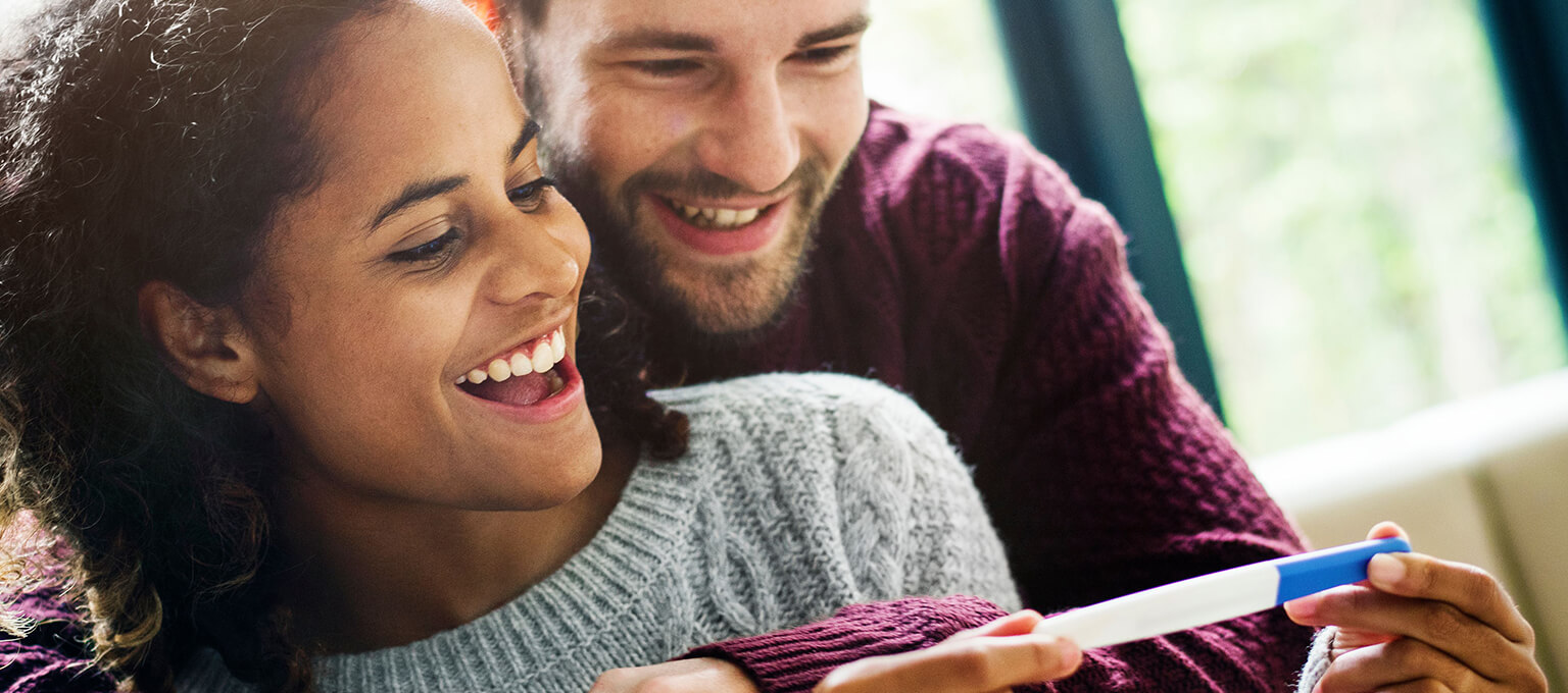 Paar hält Ergebnis Schwangerschaftstest in der Hand