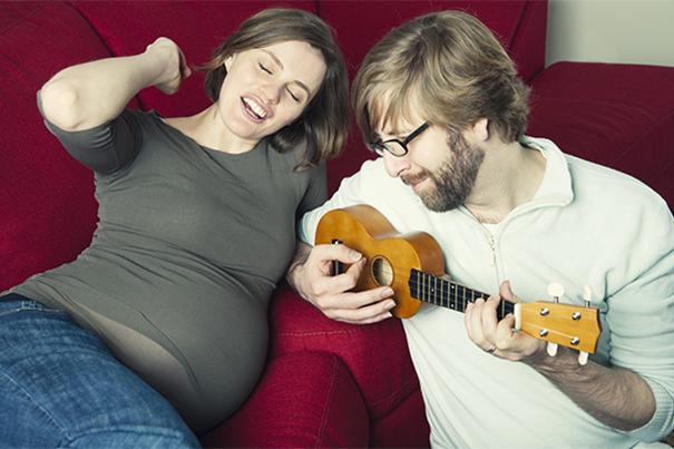 Ein Mann spielt Ukulele neben seiner schwangeren Frau und freut sich auf das Vater werden