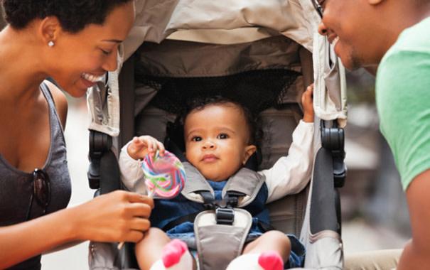 Ein Kleinkind liegt im Buggy und die Eltern lachen es an