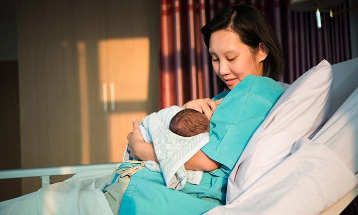 Mutter im Wochenbett hält ihr Neugeborenes im Arm
