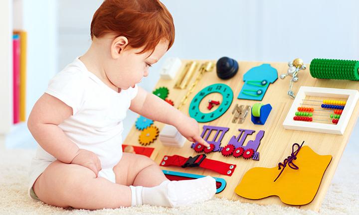 Baby entwickelt seine motorischen Fähigkeiten beim Greifspiel