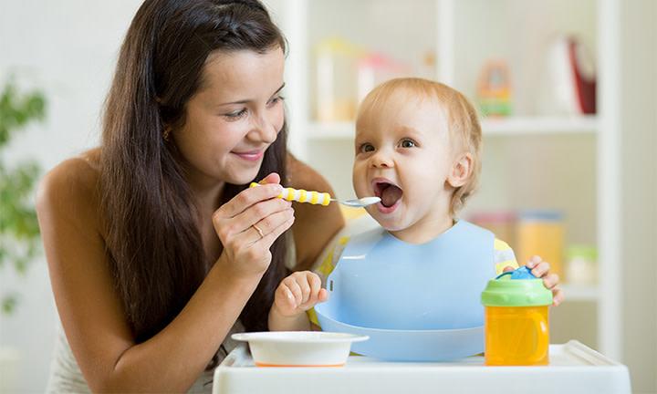 Eine Mutter füttert ihr Kleinkind mit Brei
