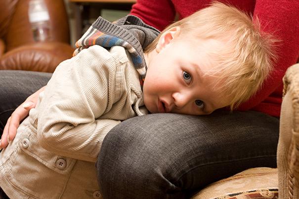 Kleinkind schmiegt sich an Mamas Bein
