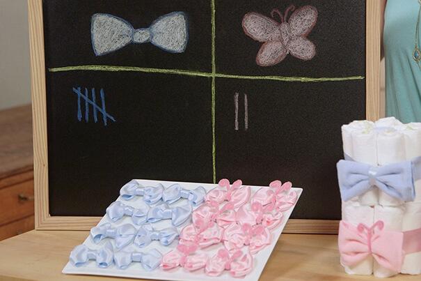 Eine Tafel sowie rosa und blaue Schleifen der Teams für tolle Babyparty-Spiele