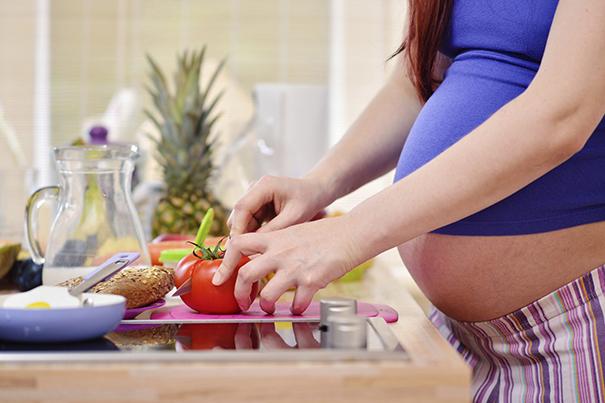 Schwangere Frau schneidet Tomate für eine gesunde Ernährung in der Schwangerschaft