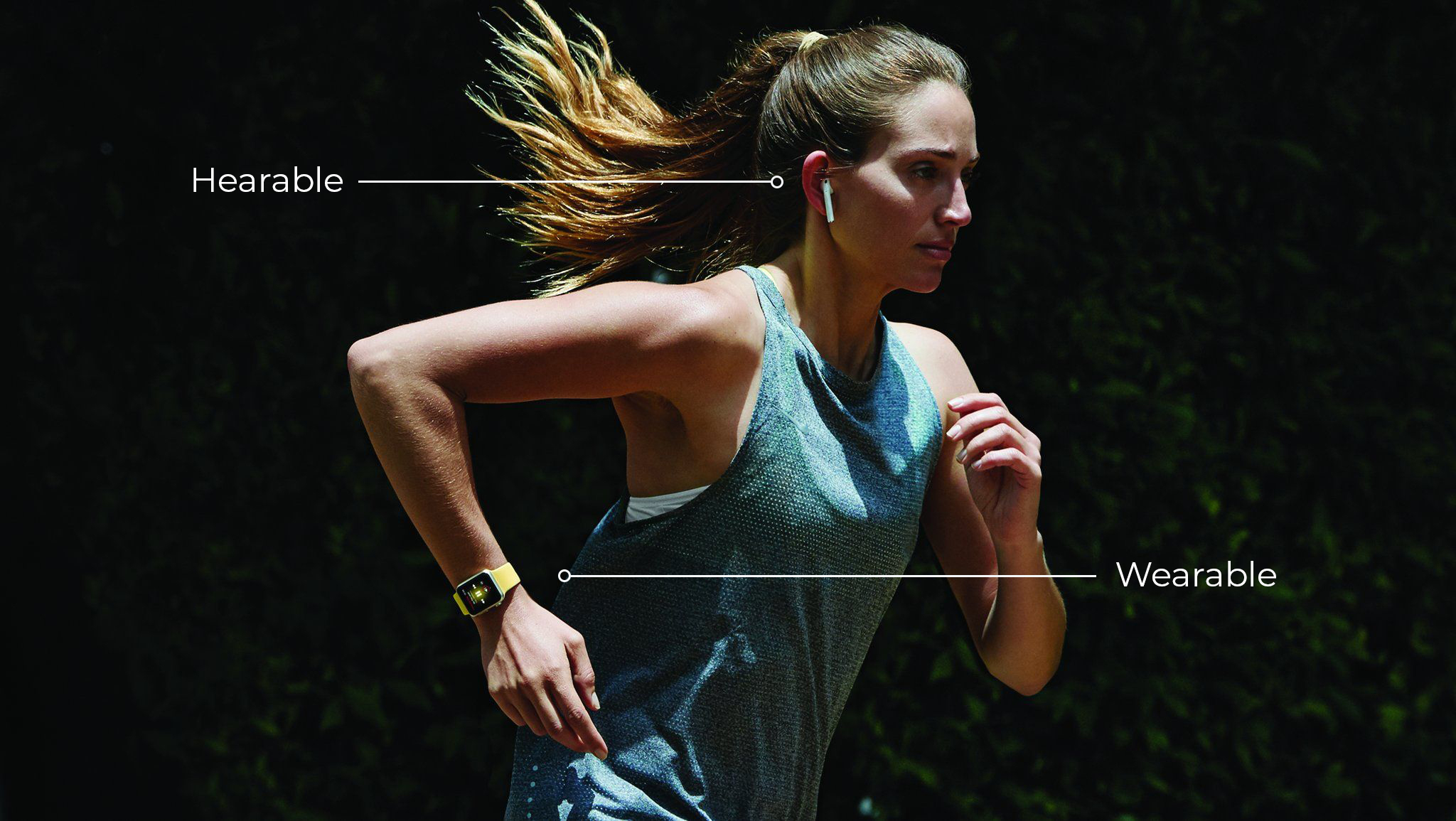 A woman jogs wearing hearables and wearables.