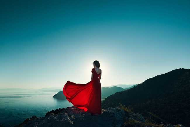 Female energy - Girl in a red dress on the mountain
