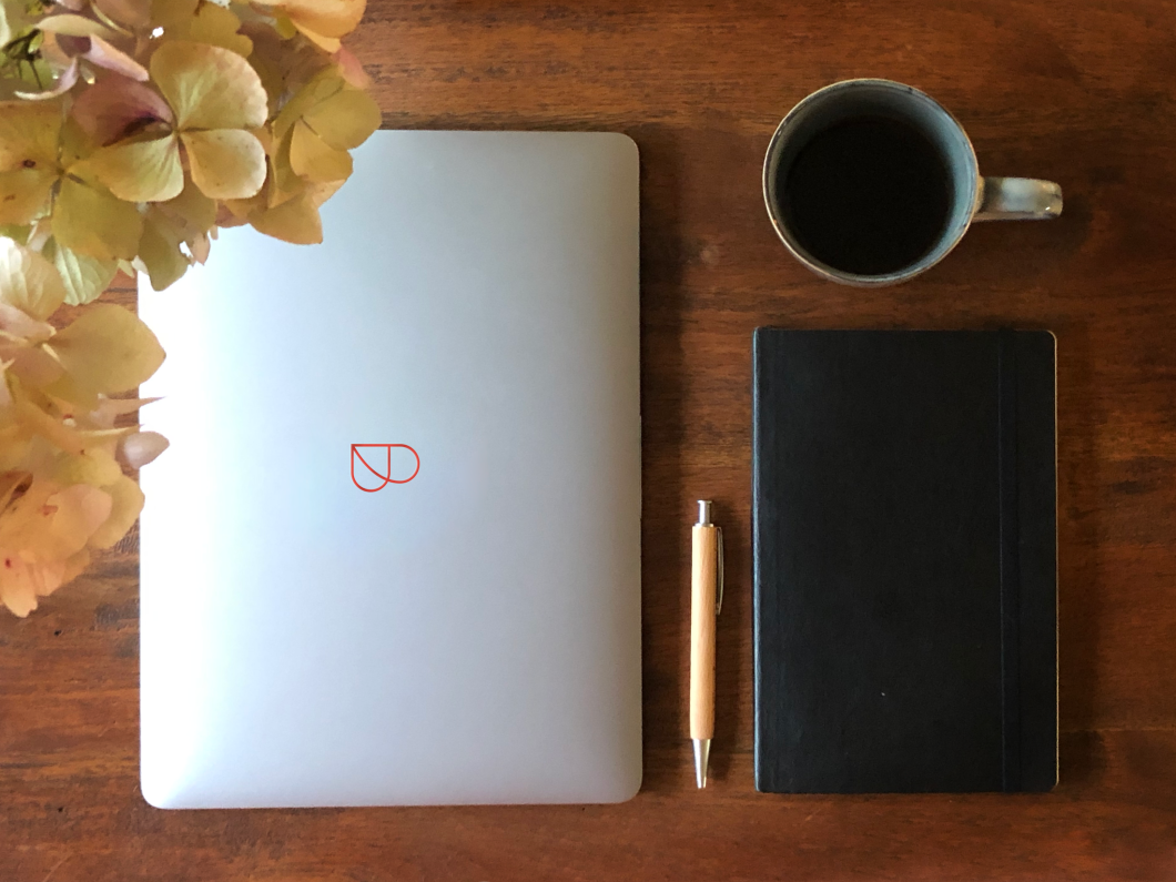 Laptop with Billie-Logo, pen, notebook and coffee on table with plant