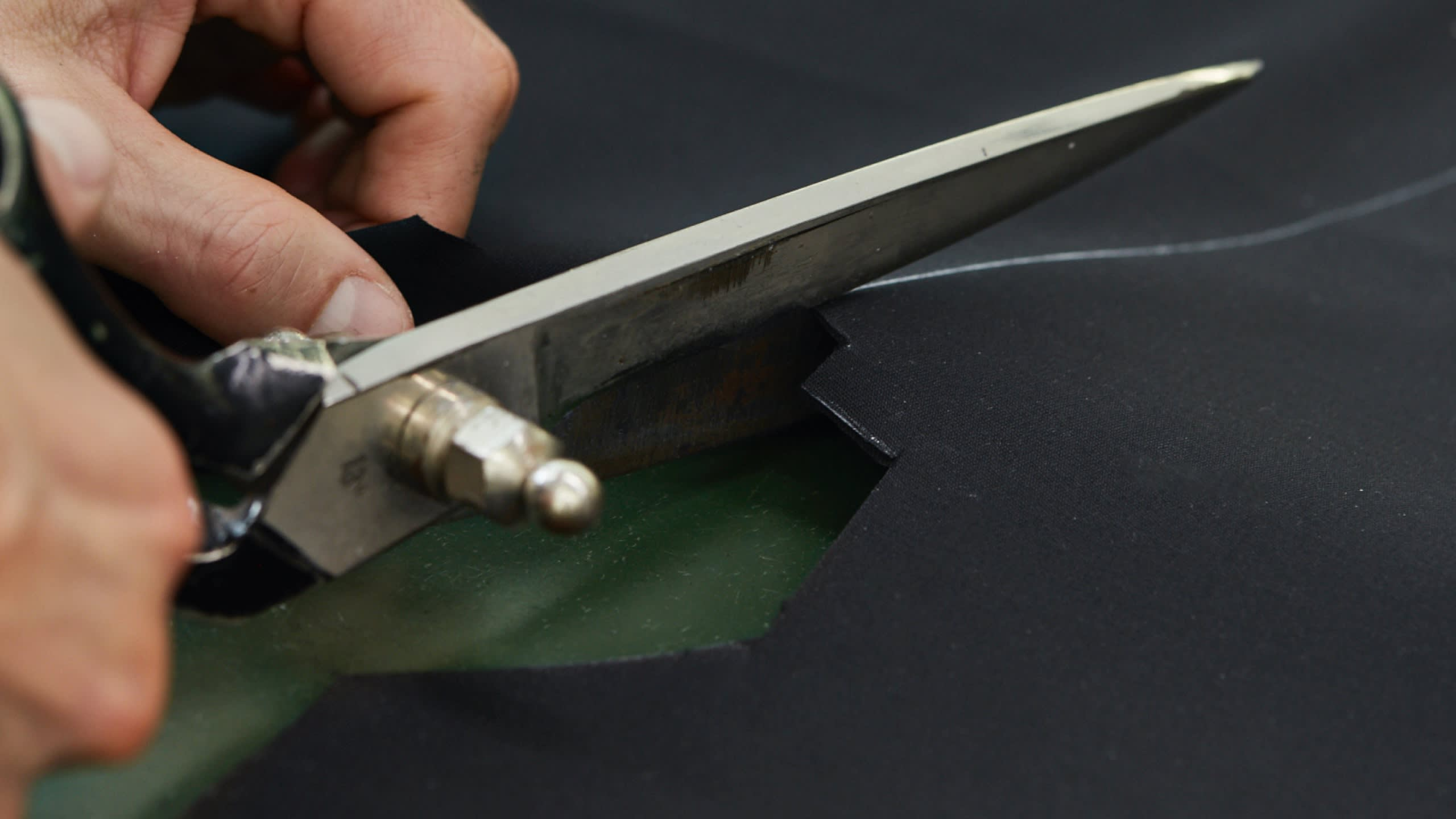 A Brioni artisan cutting a fabric