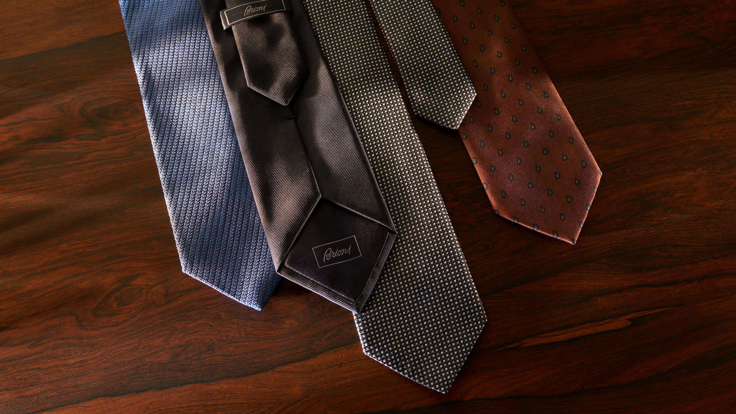Four Brioni made-to-order ties in different fabrics and patterns