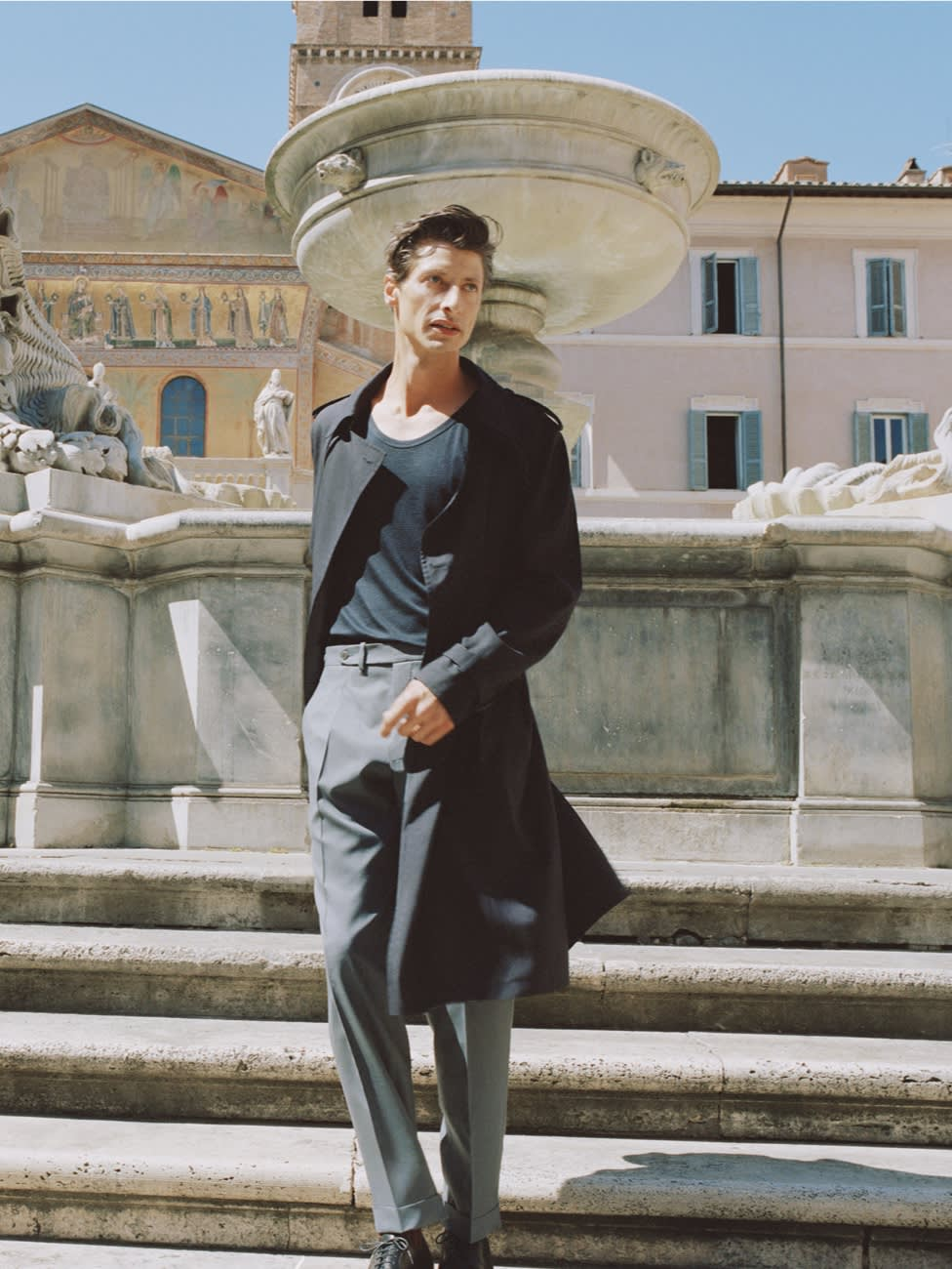 Male model wearing a dark blue trench coat and grey wool trousers