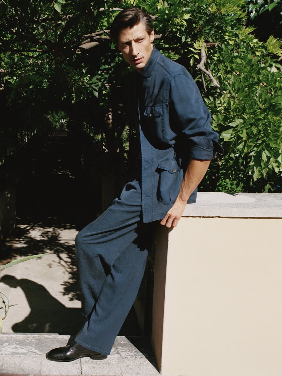 Male model wearing a navy blue washed silk sahariana and trousers