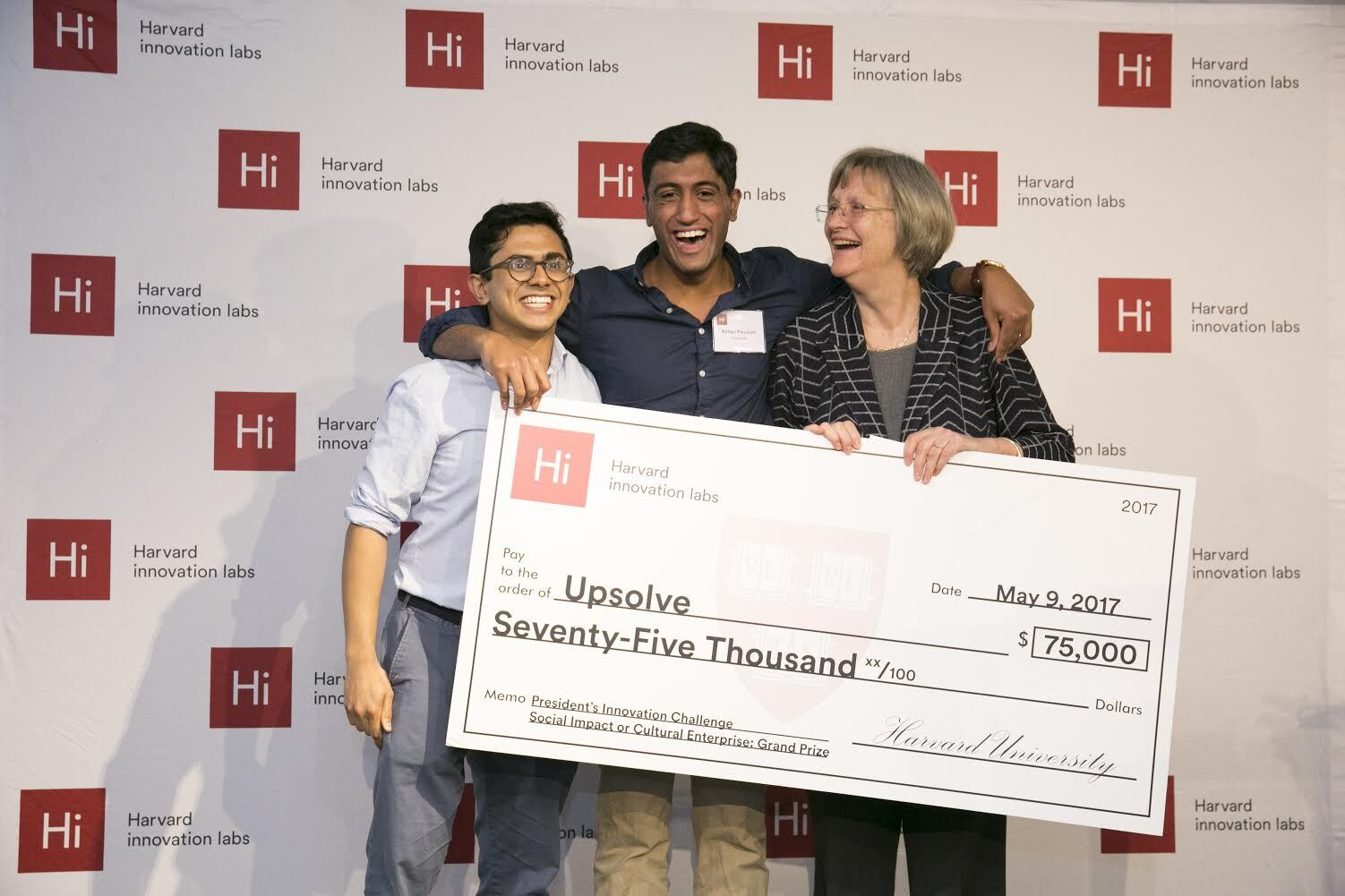 Upsolve CEO Rohan Pavuluri accepts $75,000 Grand Prize from Harvard President Drew Faust; also pictured is Milton Syed, engineer.