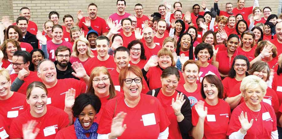 large group of people wearing red shirts waving at the camera