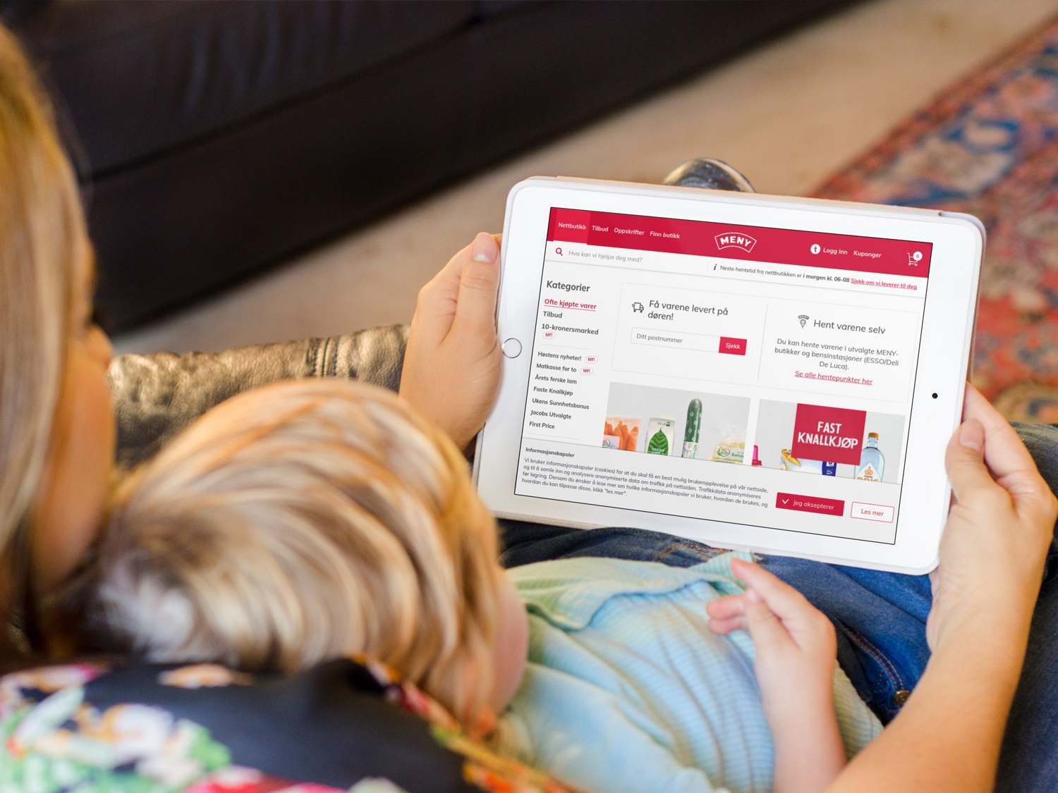 A woman sitting with her child, shopping at the Meny Netthandel website.