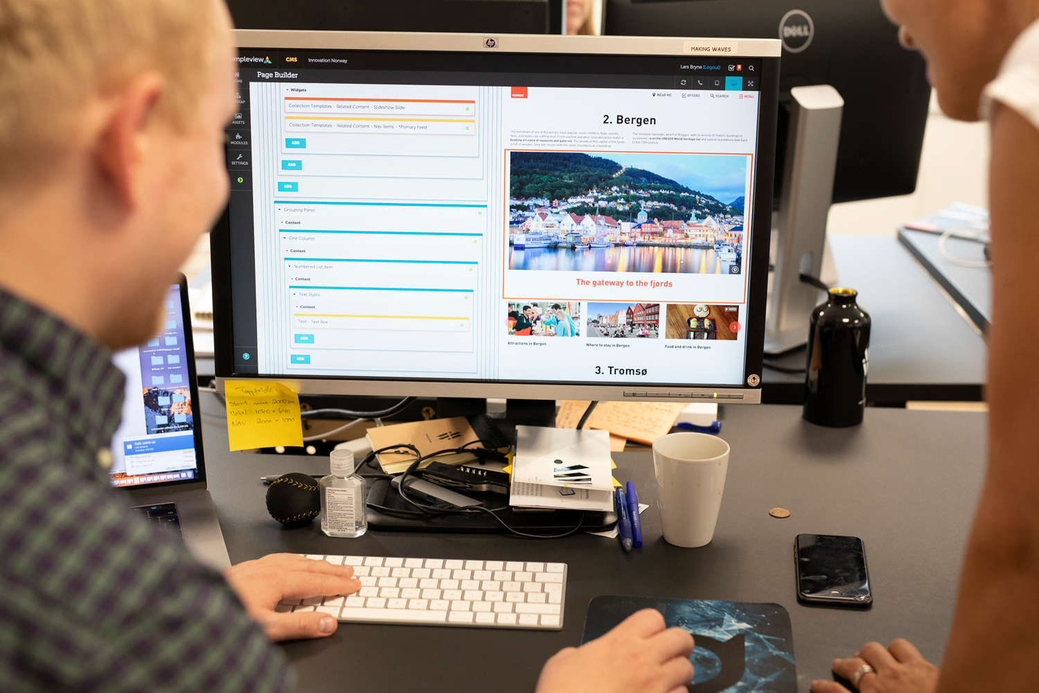 Two team members working together on Visitnorway.com on a computer screen.