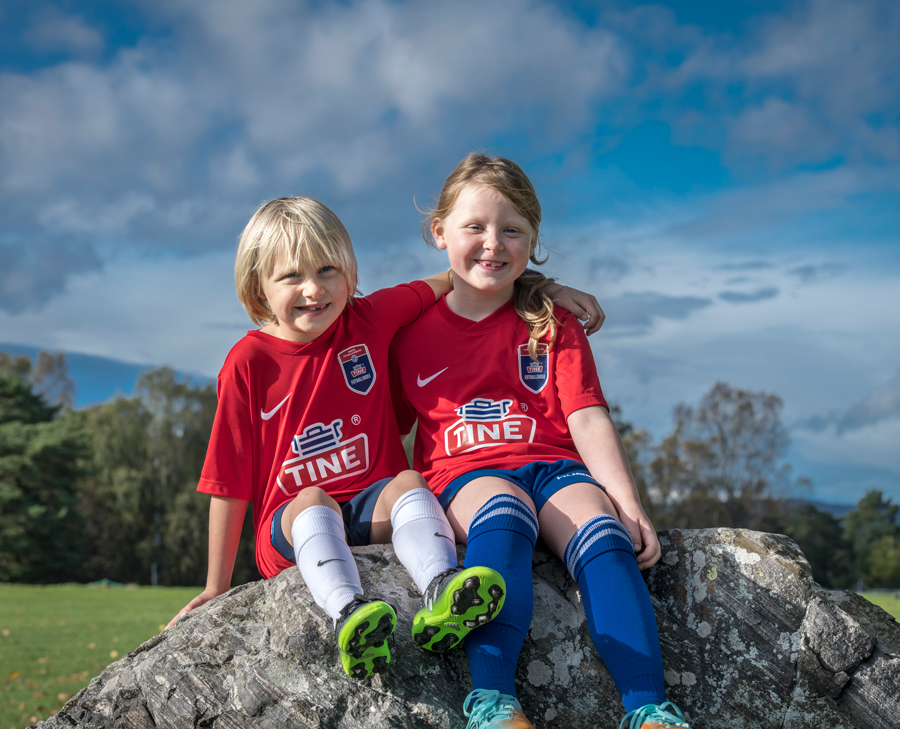 Two kids sitting on a boulder in soccer uniforms, their arms around each other.