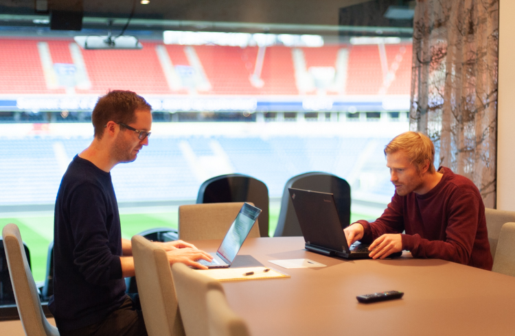Two team members working in an office overlooking a soccer stadium.