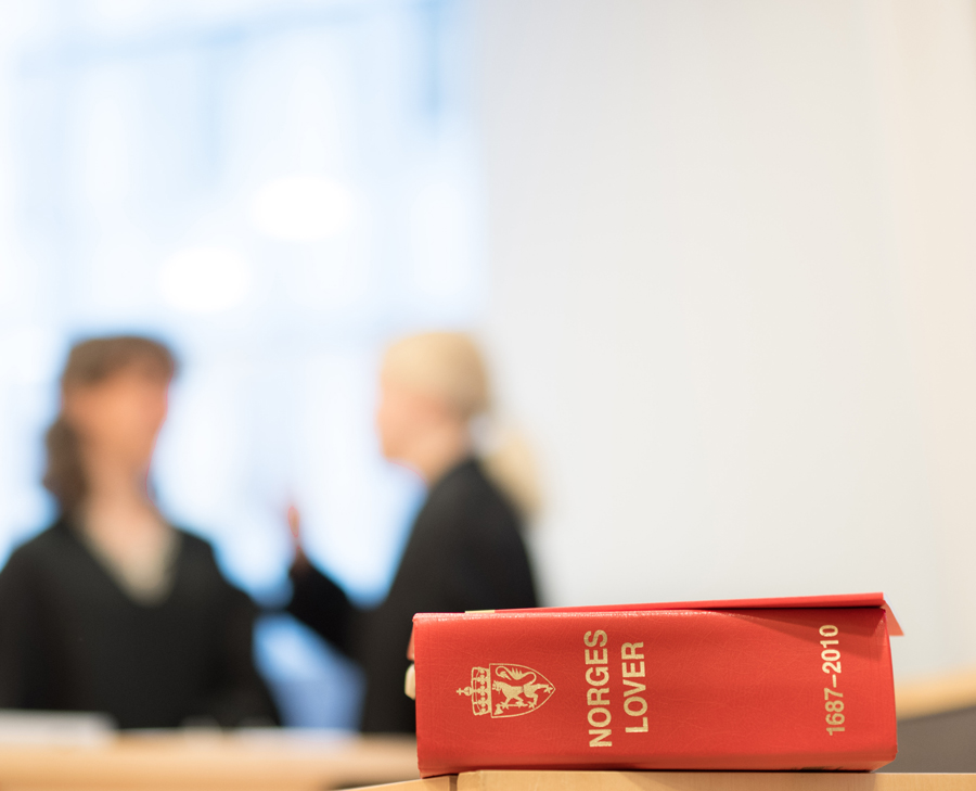 Two women discussing in the background, with the book of Norwegian laws in the foreground.