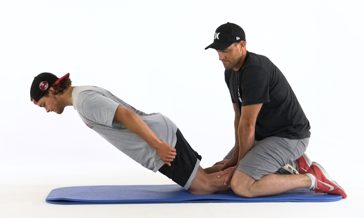 One man getting help from a second man to do warm-up exercises on a yoga mat.