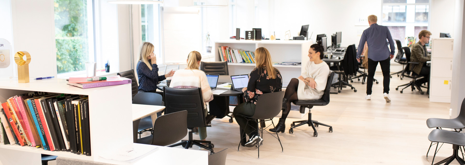 Many people working at the Oslo office - some sitting in a group, others by their desks.