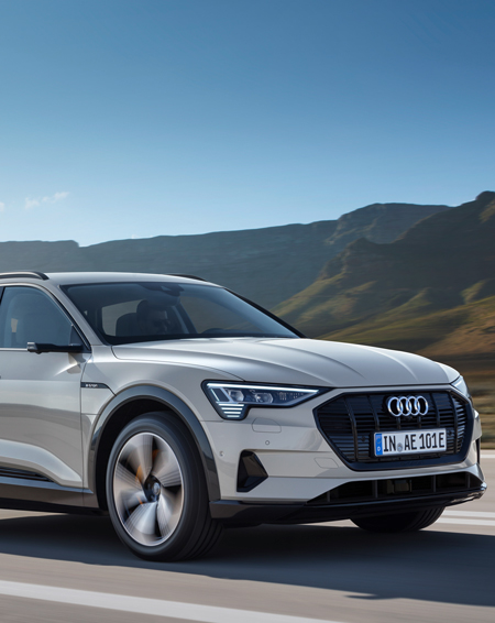 A silver Audi e-tron going down a scenic country road.