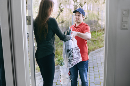 A man delivering groceries from Meny to a woman's front door.