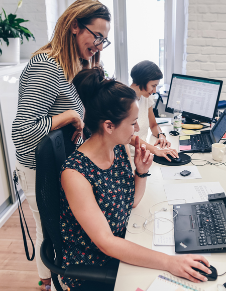 People working in the Kraków office. Two women in the foreground, looking at one computer screen, and another in the background.