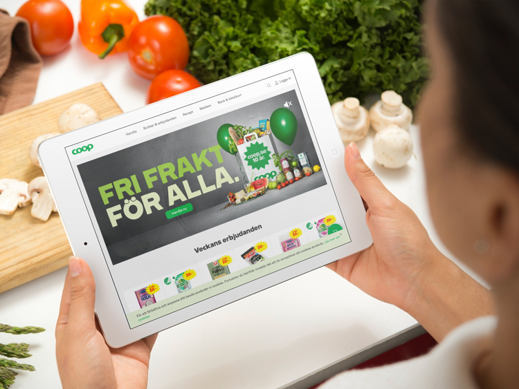 A person accessing the coop.se website on their iPad while chopping vegetables.
