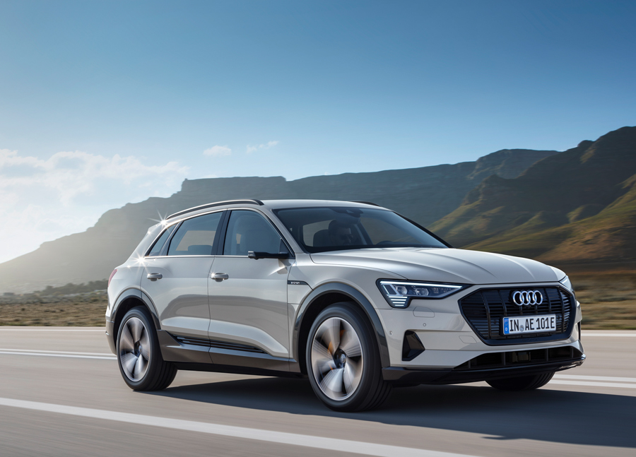 A silver Audi e-tron being driven down a scenic highway.