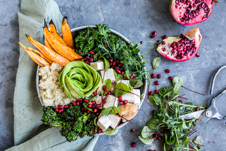 A bowl with sweet potatoes, avocado, salad and pomegranate on a table.