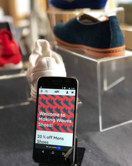 The shopping experience Making Waves created with Episerver, displayed on a phone in a store.
